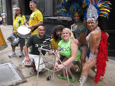 A seven people are seen at Chicago's annual Disability Pride Parade in 2011. In the center, a woman with a visible physical disability sits next to a walker while other attendees in costume hold instruments around her.